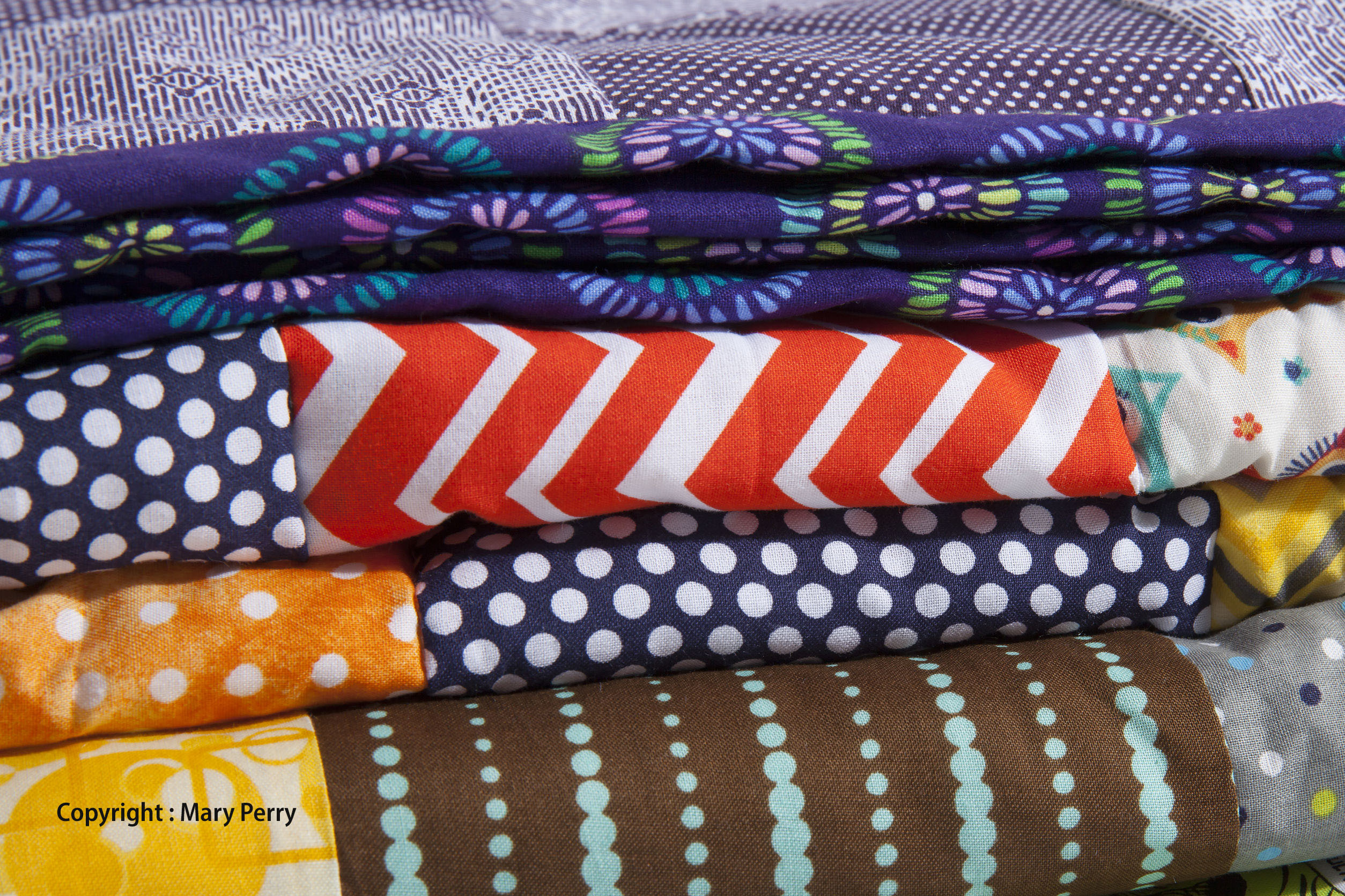 39550917 - a close up of stacked quilts showing different patterns and cloth texture.
